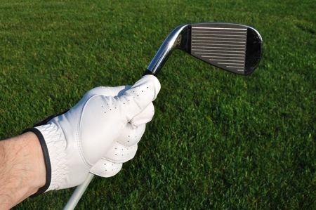Porter un gant de Golf tenant un fer à repasser (Golf Club) avec Fairway en arrière-plan de golfeur. Banque d'images - 7067671
