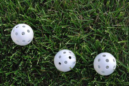 Three White Plastic Wiffle Perforated Golf Balls on Grass
