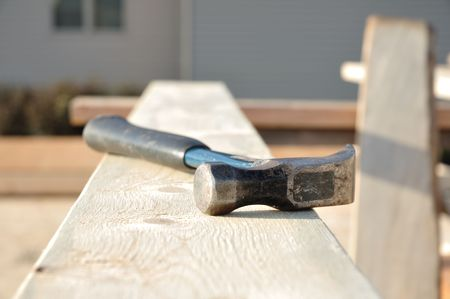 sawhorse: Shallow Focus on Claw Hammer on Board at Construction Site