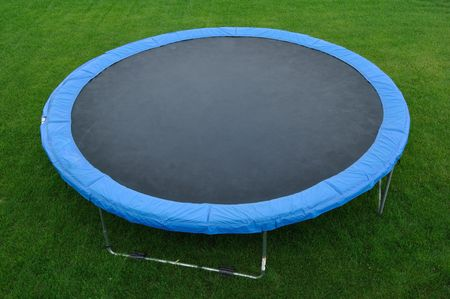 A Round Trampoline on the Back Yard Grass Banco de Imagens