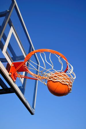 hoops: Basketball Shot Falling Through the Net, Blue Sky, vertical, copy space