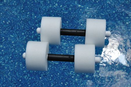 Pair of Water Aerobics Dumbbells Floating in a Swimming Pool