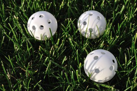 perforated: Three White Plastic Wiffle Perforated Golf Balls on Grass