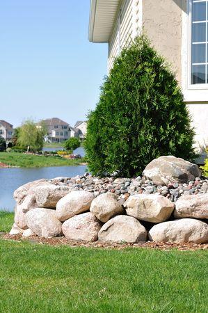 石造りの擁壁と住宅家庭で常緑低木 写真素材