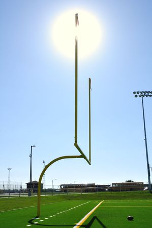 yardline: Sun Behind Goal Posts on American Football Field