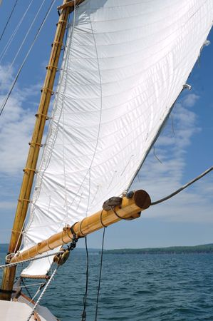 schooner: Foresail and Wooden Mast of Schooner Sailboat on a Sunny Summer Day