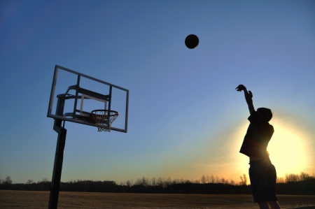 outside shooting: Silhouette of a Teen Boy Shooting a Basketball at Sunset, copy space