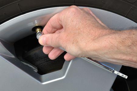 safety check: Comprobaci�n de la presi�n de aire de un neum�tico con un medidor de presi�n de neum�ticos  Foto de archivo