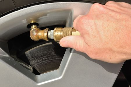 Automobile Maintenance - Inflating a Car Tire with Air  Stock Photo - 7917826