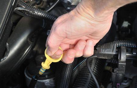 自動車メンテナンス - エンジン ディップスティック油をチェックするレベルを引っ張る 写真素材