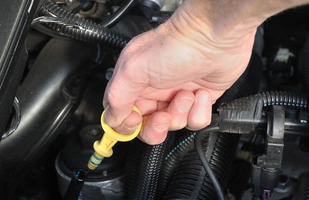 Automobile Maintenance - Pulling the Engine Dipstick to Check the Oil Level Stock Photo