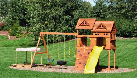 Back Yard Wooden Swing Set on Green Lawn 写真素材