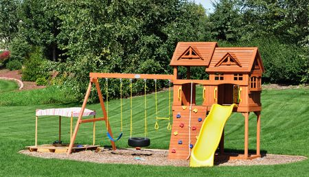 Back Yard Wooden Swing Set on Green Lawn Stock Photo