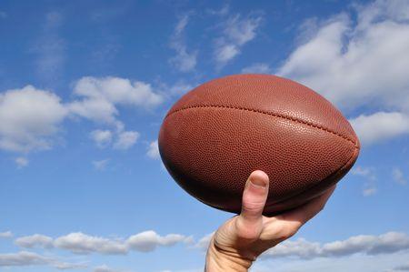 jugadores de futbol: Quarterback Throwing un f�tbol americano contra un cielo azul