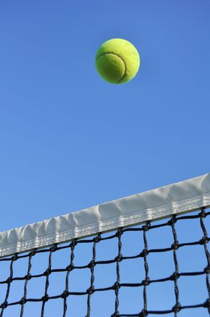 net: Yellow Tennis Ball Flying Over the Net Against a Clear Blue Sky