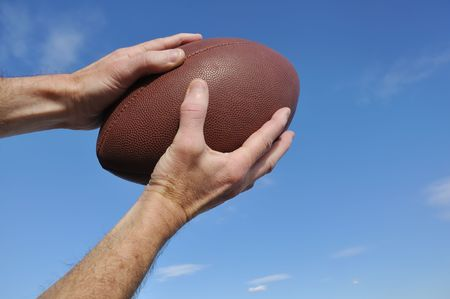 Receiver Catching an American Football Pass Against a Blue Sky Stock Photo