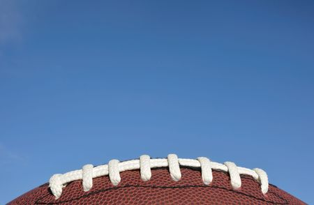american football: Close-up of American Football Laces Against a Clear Blue Sky