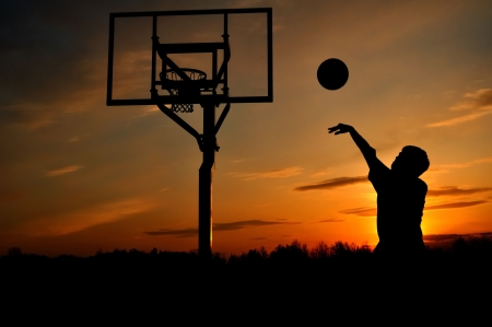 outside shooting: Silhouette of Teen Boy Shooting a Basketball at Sunset, copy space