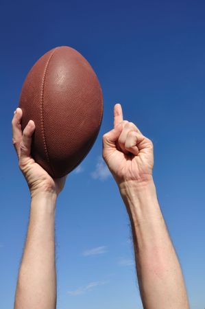 grasp: American Football Player Celebrates a Touchdown Holding a American Football and Giving a Number One Sign