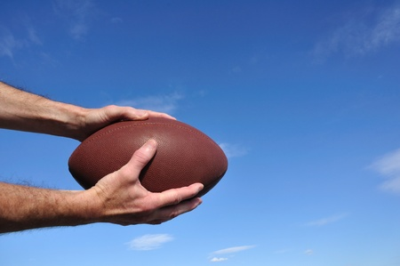 grabbing hand: Receiver Catching an American Football Pass Against a Blue Sky Stock Photo