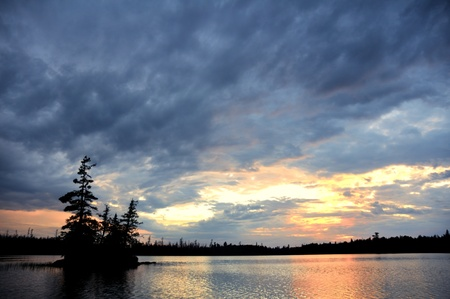 Scenic Island on a Remote Wilderness Lake with Dramatic Sky at Sunset photo