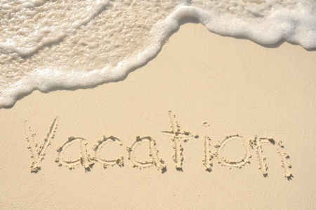 The Word Vacation Written in the Sand on a Beach