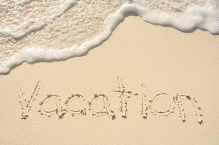 sandy: Las vacaciones de la palabra escrita en la arena en una playa