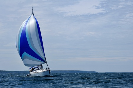 Sailboat with blue spinnaker Sail on a beautiful summer day, horizontal