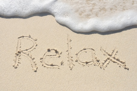 The Word Relax Written in the Sand on a Beach Stock Photo