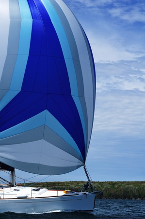 Sailboat with blue spinnaker Sail on a beautiful summer day, vertical photo