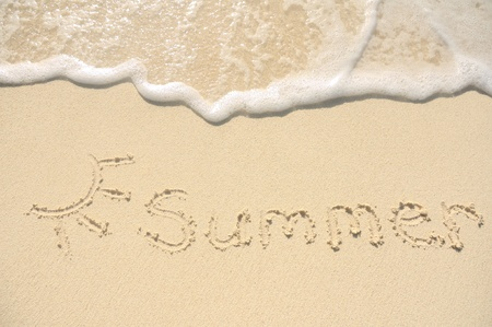 The Summer Written in the Sand on a Beach with Drawing of the Sun photo