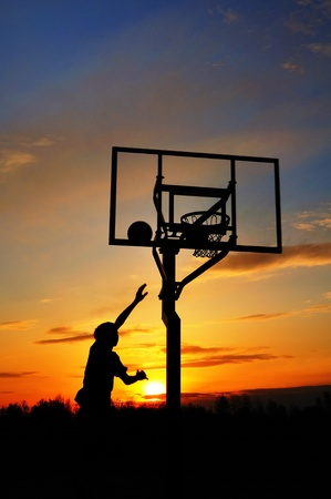Silhouette of Teen Boy Shooting a Basketball at Sunset, copy space,vertical photo