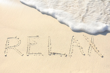 The Word Relax Written in the Sand on a Beach 版權商用圖片