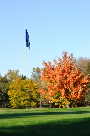Golf Flagstick with Colorful Fall Leaves of Maple Trees photo