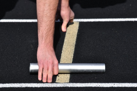 starting line: Hand Holding a Baton at the Starting Line at a Track Meet Stock Photo