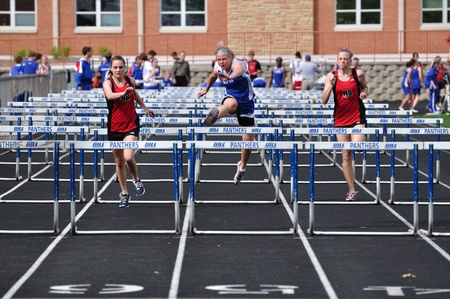 SPRING LAKE PARK, MN - May 7: Unidentified Teen Girls Competing in High School Hurdles Race on May 7, 2010 in Spring Lake Park, Minnesota.