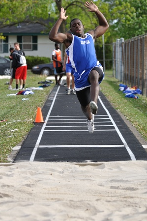 SPRING LAKE PARK, MN - May 7: Unidentified Teen Boy Doing the Long Jump at a High School Track and Field Meet on May 7, 2010 in Spring Lake Park, Minnesota. Stock Photo - 9532390