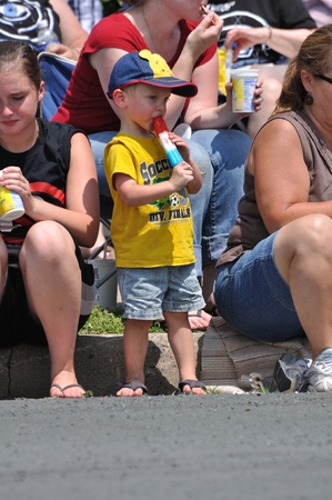 OSSEO, MN - JUNE 26 : Unidentified Young Boy Eating a Frozen Treat While Watching  the Osseo Marching Band Festival on June 26, 2010 in Osseo, MN