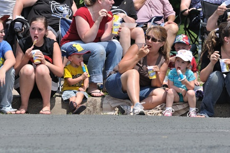 OSSEO, MN - JUNE 26 : Unidentified Family Eating Frozen Treats While Watching  the Osseo Marching Band Festival on June 26, 2010 in Osseo, MN