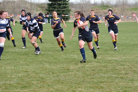 BLAINE, MN - APRIL 30: Unidentified Navy player running with ball in womens collegiate rugby match between Navy & the BYU Cougars in the NCAA Division I College Championship quarterfinals on April 30, 2011 in Blaine, MN