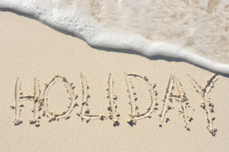 The Word Hoilday Written in the Sand on a Beach photo