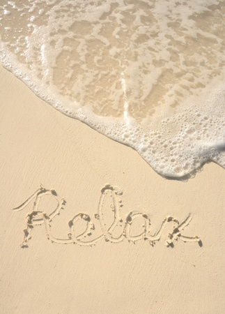 The Word Relax Written in the Sand on a Beach photo
