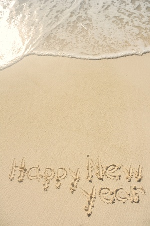 sand writing: The Phrase Happy New Year Written in the Sand on a Beach