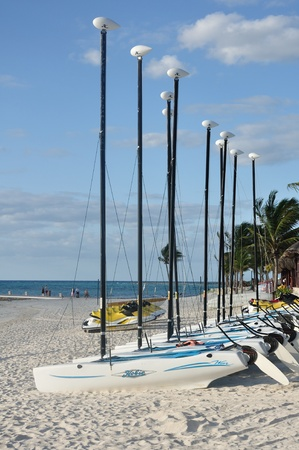 hobie: PUERTO AVENTUARAS, MEXICO - March 13: Hobie Cat Sailboats on a Tropical Beach on a Sunny Morning at a Resort in Mexicos Riviera Maya on March 13, 2011 in Puerto Aventuras, Mexico