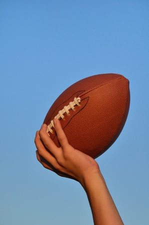 tosses: Quarterback Throwing an American Football Against a Blue Sky