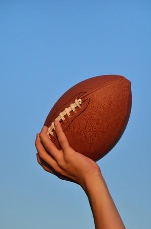 offense: Quarterback Throwing an American Football Against a Blue Sky