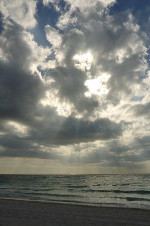 crepuscular: Crepuscular Rays Trough the Clouds on a Sandy Beach on the Caribbean Sea