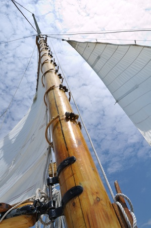 schooner: Foresail, Jib, and Wooden Mast of Schooner Sailboat on a Sunny Summer Day Stock Photo