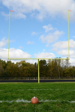 Yellow Goal Posts and Football on American Football Field photo