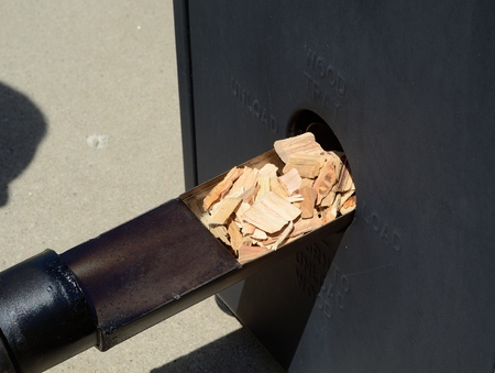 smoker: Putting Hickory Wood Chips in a Barbecue Smoker Stock Photo